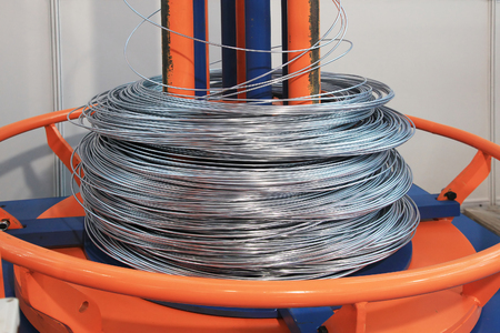 unwinding and feeding wire into the machine for alignment and cutting construction rebar