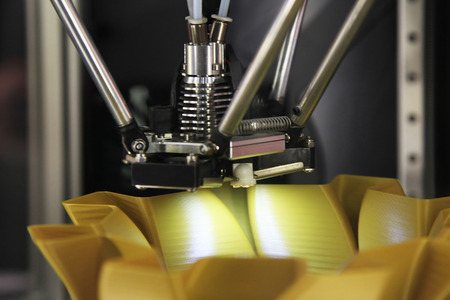 Modern 3D printer printing figure close-up macro. Automatic three dimensional 3d printer performs plastic brown colors modeling in laboratory. Stock Photo