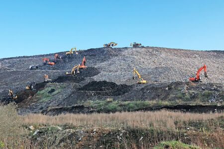 Reclamation of solid waste landfill by heavy machinery