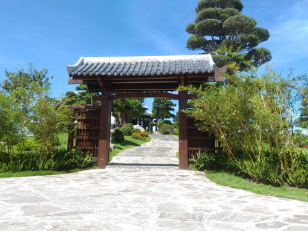 Gate in the Chinese style, growing bamboo, a path leading to the house, shrub blossoms, tall tree, green lawn Asia, Vitnam Park on Winperl Island Standard-Bild