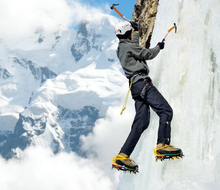 crampon: Man climbing on icefall in winter mountains