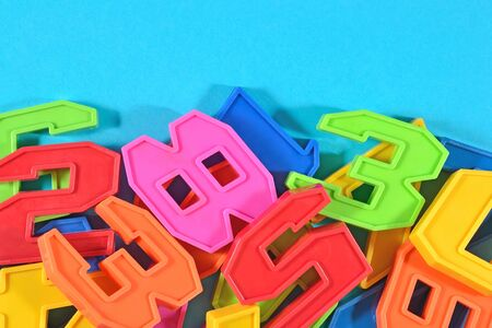 numeracy: Heap of plastic colored numbers on a blue background close up