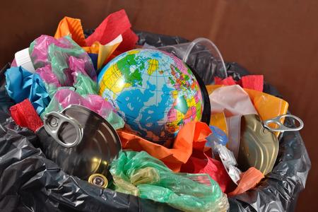 Globe in de vuilnisbak. Conceptueel beeld over het opslaan van de aarde.