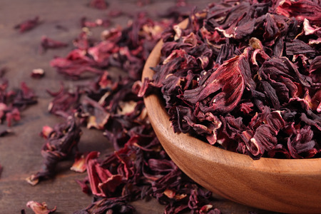 Dried petals of hibiscus in a wooden bowl close up