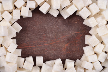 refined: Frame of refined sugar on a wooden background