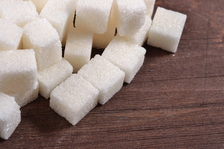 refined: Heap of refined sugar on a wooden background