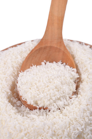 shredded coconut: Shredded coconut in a wooden spoon on a white background