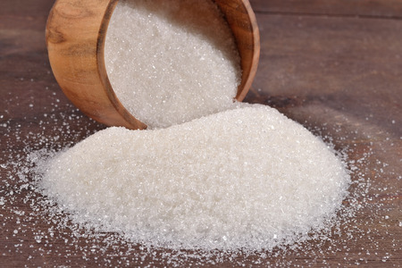 sucrose: White sugar in a wooden bowl