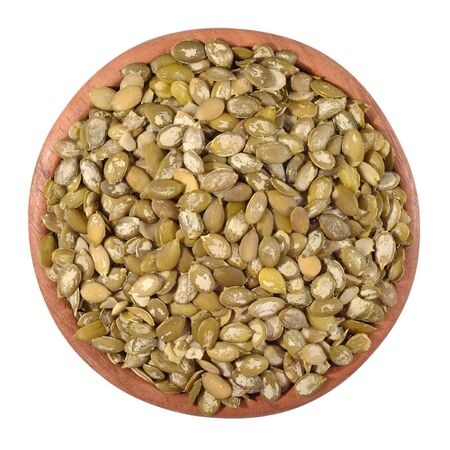 cleared: Cleared pumpkin seeds in a wooden bowl on a white background