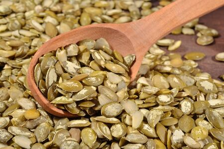 cleared: Cleared pumpkin seeds in a wooden spoon Stock Photo