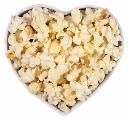Fresh popcorn in plate in the form of heart on a white background photo