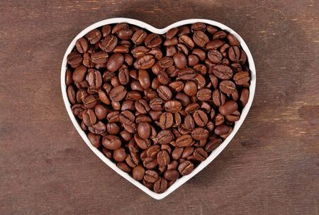 Coffee beans in plate in the form of heart in a wooden background