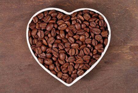 granos de cafe: Granos de café en la placa en forma de corazón en un fondo de madera