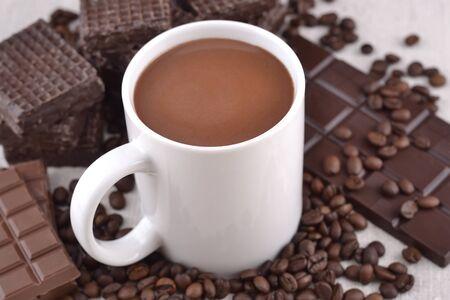 fondo chocolate: Blanco taza de chocolate caliente en los granos de caf� y chocolate de fondo