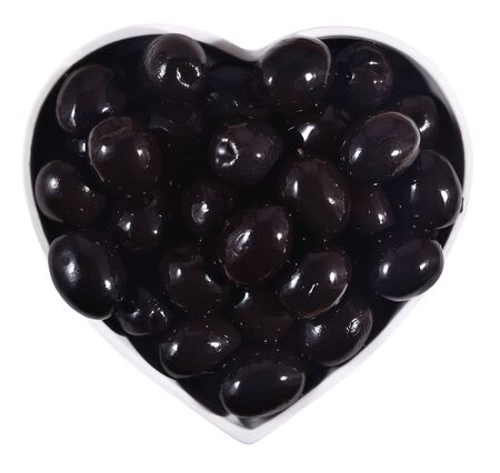 Black olives in plate in the form of heart on a white background photo