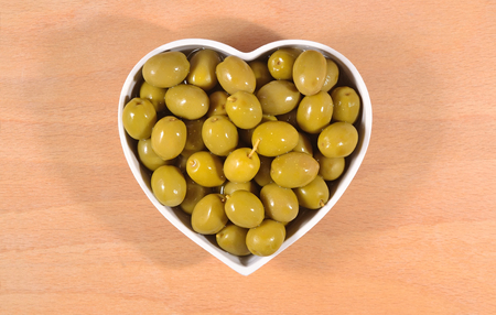 Green olives in plate in the form of heart