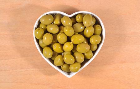 Groene olijven in de plaat in de vorm van hart