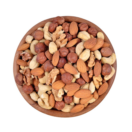 Assorted nuts in a wooden bowl isolated on a white background