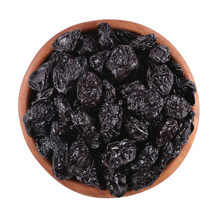 Prunes in a wooden bowl on a white background