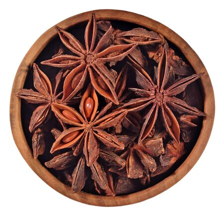 anice: Star anise in a wooden bowl on a white background Stock Photo