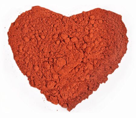 chili powder: Ground paprika in the form of heart on a white background