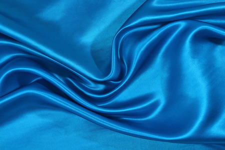 Background from a blue satin fabric with picturesque folds Stock Photo