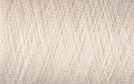 fibrous: Spool of white thread macro background texture