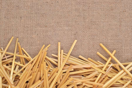 Straw on burlap as background texture photo