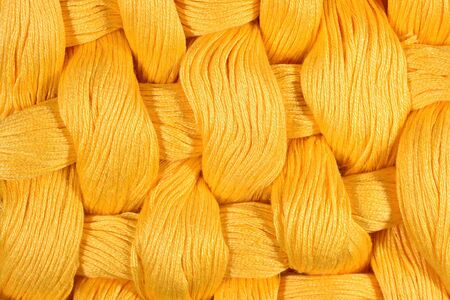 texture twisted: Yellow twisted skeins of floss as background texture close up