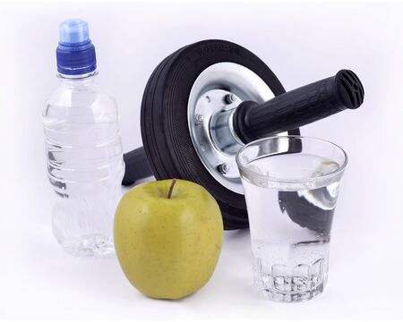 overeat: Bottle of water green apple glass of water and roller wheel for abdominals on a white