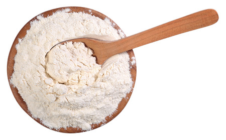 Top view of white flour in a wooden bowl with spoon on a white background