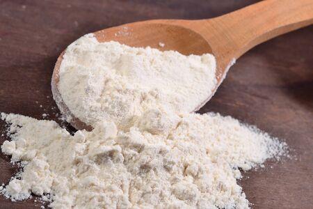 white flour: White flour in a wooden spoon close up Stock Photo