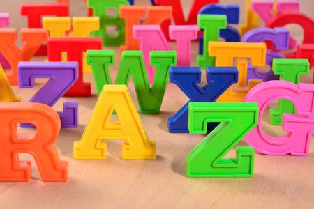 lettres alphabet: Plastique lettres de l'alphabet color� gros plan sur un fond de bois Banque d'images