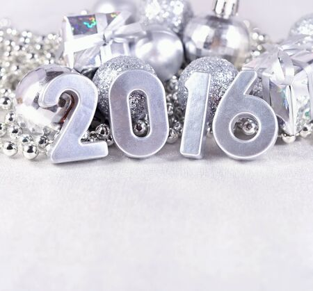hristmas: 2016 year silver figures on the background of silvery Сhristmas decorations