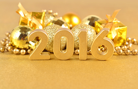 2016 year golden figures on the background of golden Christmas decorations Imagens