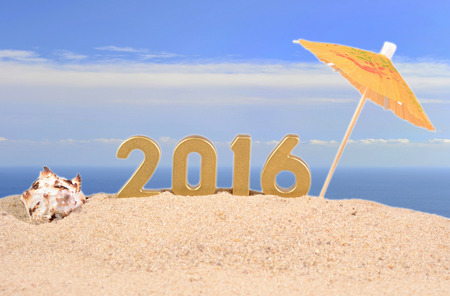 2016 year golden figuresl on a beach sand against the background of the sea Imagens