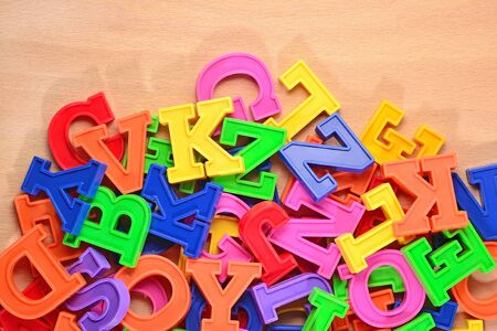 abstract academic: Colored plastic alphabet letters on a wooden background