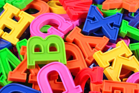 abstract academic: Heap of plastic colored alphabet letters close up as background