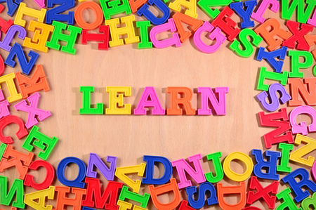 ideas: Learn written by plastic colorful letters on a wooden background Stock Photo