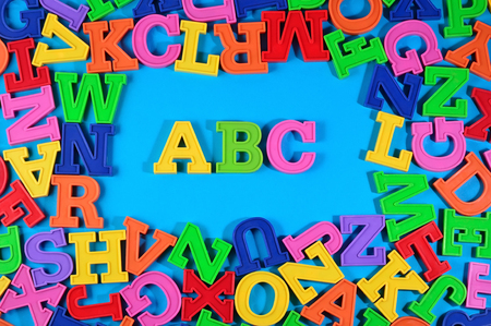 abstract academic: Plastic colored alphabet letters ABC on a blue background