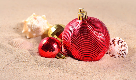 golden ball: Christmas decorations and seashells on a beach sand