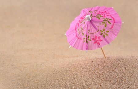 cocktail umbrella: Cocktail umbrella close-up on a sand background
