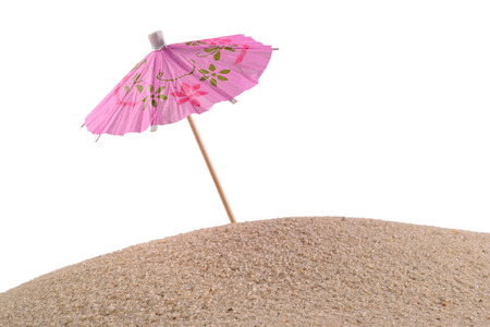 cocktail umbrella: Cocktail umbrella in sand on a white background