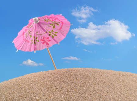 cocktail umbrella: Cocktail umbrella on a beach sand against the blue sky