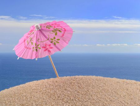 cocktail umbrella: Cocktail umbrella on a beach sand against the background of the sea