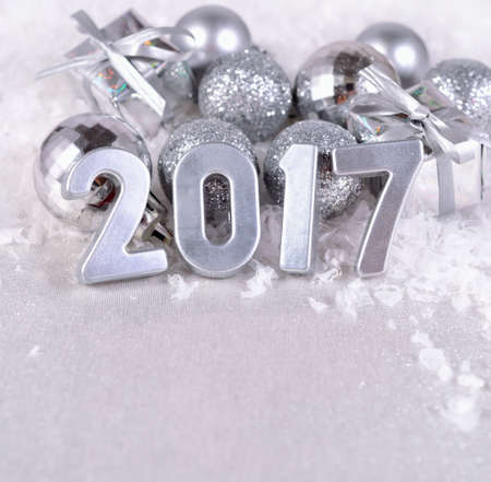 argent: 2017 year silver figures on the background of silvery Christmas decorations