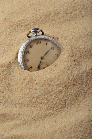 sand watch: Antique pocket watch in sand on the beach Stock Photo