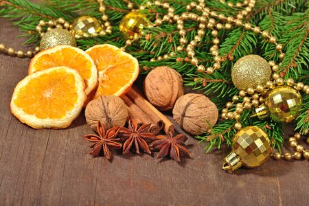 Different kinds of spices, nuts and dried oranges, Christmas decorations and spruse branch on a wooden background