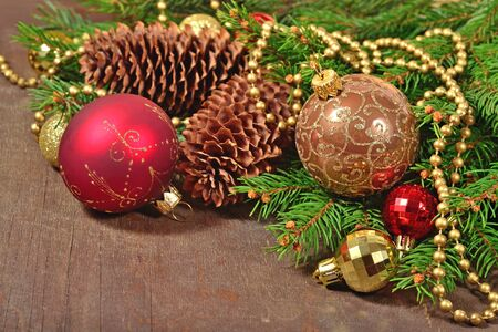 Christmas decorations and spruce branch and cones on a wooden background Stock Photo