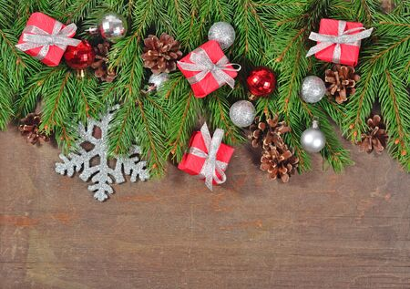 Silver and red Christmas decorations and spruce branch and cones on a wooden background